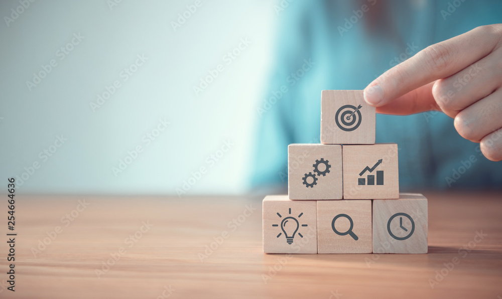 Fototapeta Businesswoman hand arranging wood block with icon business strategy and Action plan, copy space.