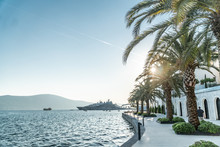 Pier Near The Sea In A European Resort Town With Palm Trees On The Shore And The Mountain And Yachts In The Background. Horizontal Shot