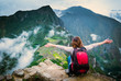 View of girl sitting on the edge of the rock with raised hands and taking pleasure of breathtaking forested mountains landscape of Machupicchu