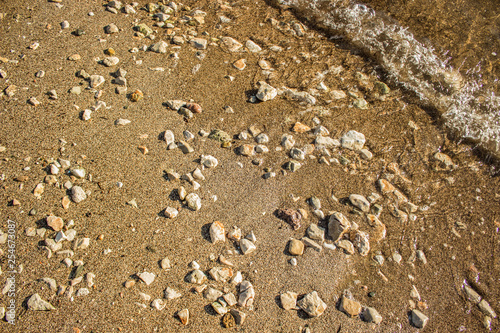 Fotografía  sand stone beach shoreline nature background surface from above near wave photog