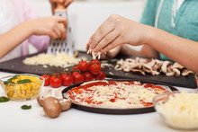 Young Hands Prepare Pizza At Home - Grate And Sprinkle The Cheese