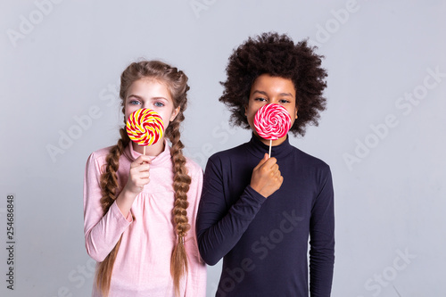 Fotografía  Cute good-looking kids holding sweets and covering half of the face