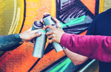 Fototapeta Młodzieżowe - Group of graffiti artists stacking hands while holding spray color can against mural background - Young painter at work - Concept of contemporary art, street art and people youth lifestyle