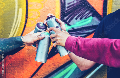 Group of graffiti artists stacking hands while holding spray color can against mural background - Young painter at work - Concept of contemporary art, street art and people youth lifestyle - 254691875