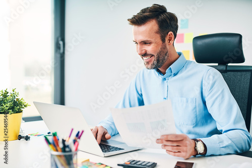 Fototapeta Happy businessman working with financail documents at office obraz