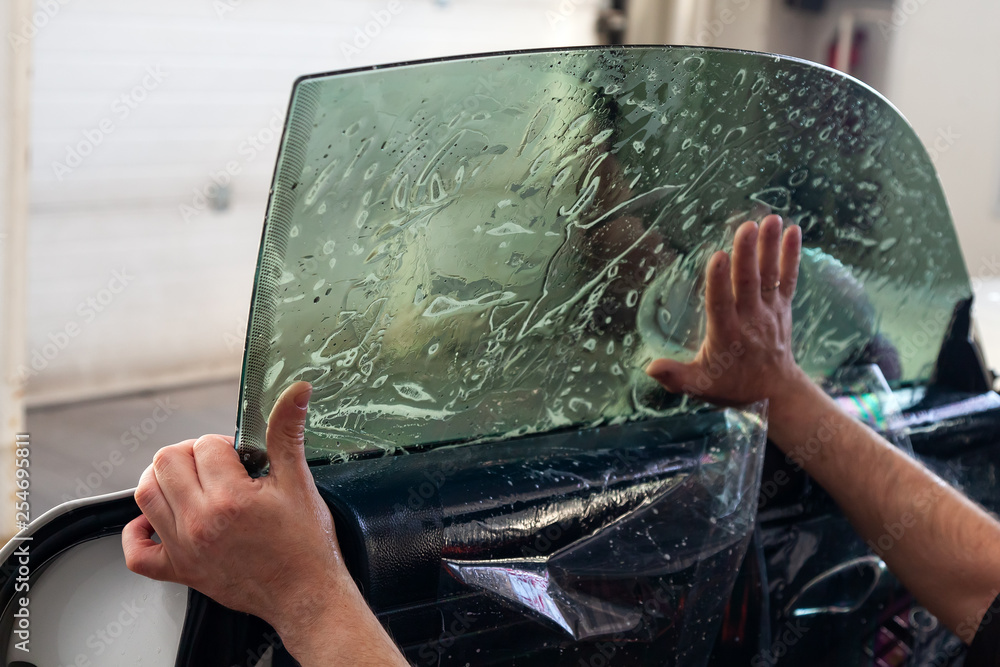 Fototapety, obrazy: The wizard for installing additional equipment sticks a tint film on the side front glass of the car and flattens it by hand to fit the glass with a greenish tint in the auto service.