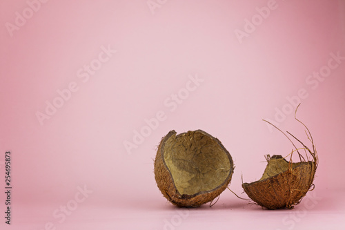 Fotografía  Chopped in half coconut on a pink background. Loss concept