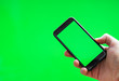 canvas print picture - Male hand with Smartphone over green screen. Place for your advertisement.