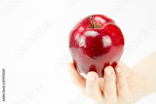 Fotografie, Obraz  Hand of a young woman holding a red apple like the one offered by the witch to S