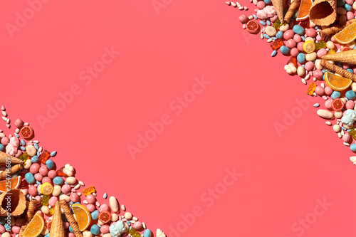 Various sweets, candys are palced on the photo on the coral background