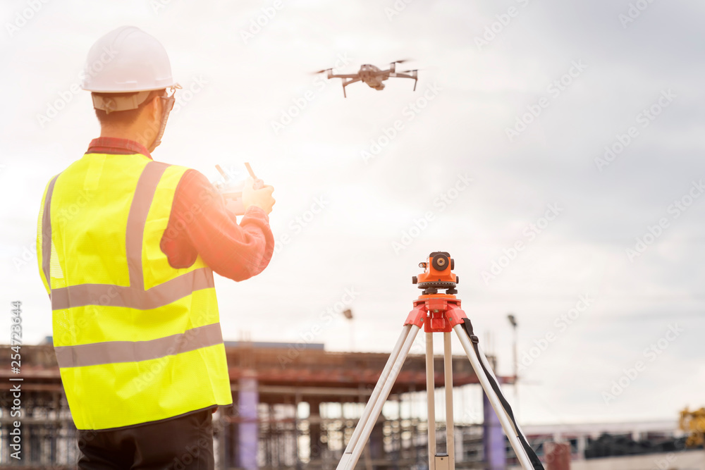 Fototapeta Engineer  working at construction Site with Drone over construction site.