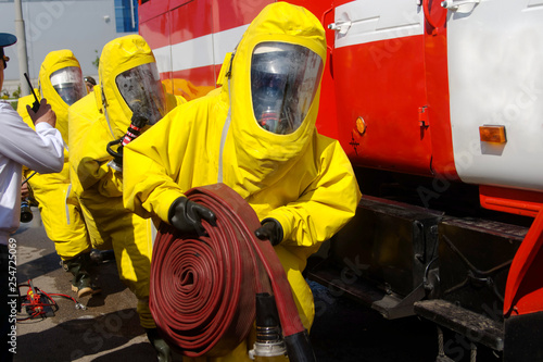 Three firefighters in protective suits and gas masks are preparing
