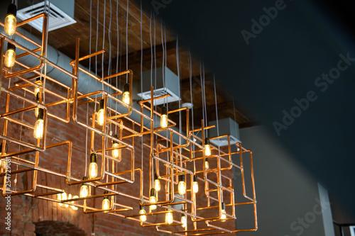 System of retro edison lamps and copper tubes in loft interior Fototapeta