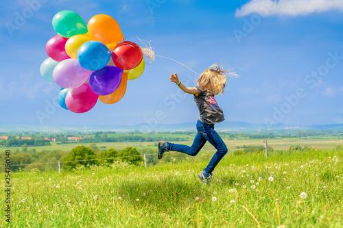 Leinwand Poster Glückliches Mädchen spring mit vielen bunten Luftballons über eine grüne Wiese