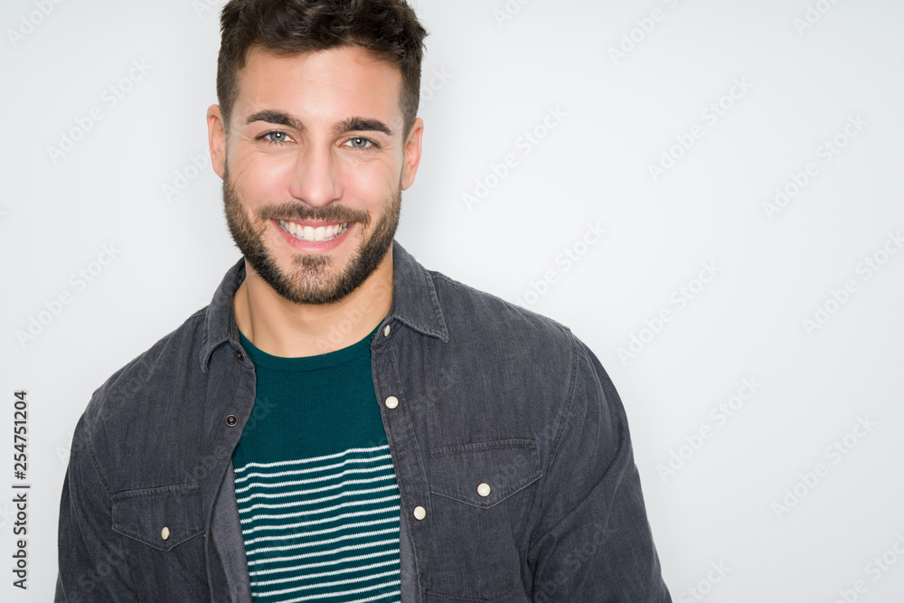 Fototapeta Young handsome man possing and modeling over grey isolated background