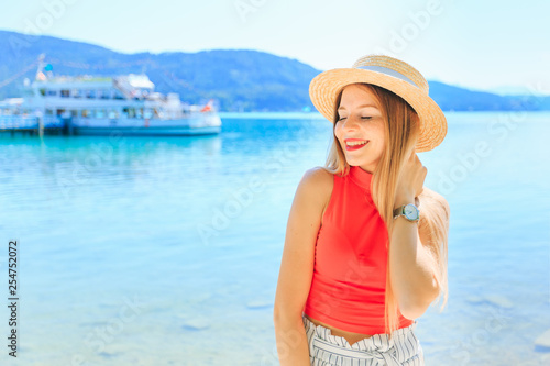 Photo close-up of a girl with boater closed her eyes and smile. lake,