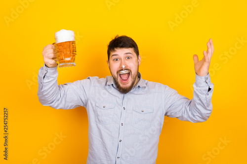 Fotografiet funny man with a glass of beer and foam on his mustache and nose on a yellow bac