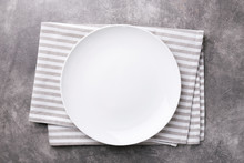 Empty Plate With Striped Napkin On Gray Stone Background. Top View.