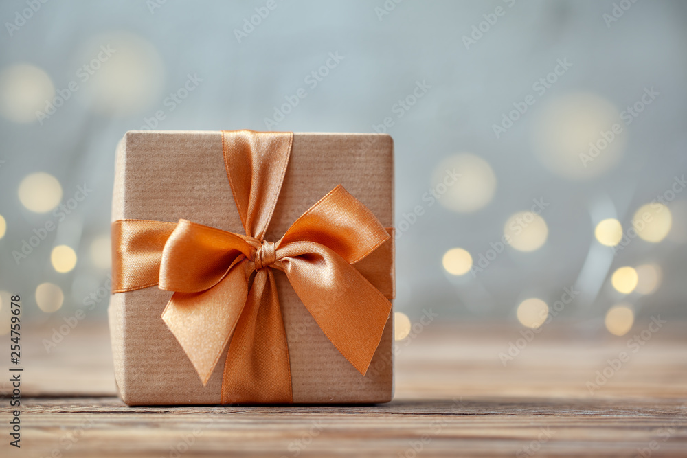 Fototapety, obrazy: Gift box wrapped with craft paper and bow on neutral background with boke.