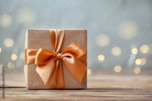 Gift box wrapped with craft paper and bow on neutral background with boke Canvas Print