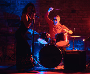 Jazz band performance. Young couple of musicians - a drummer and a singer in a nightclub.
