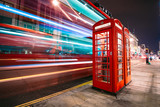 Fototapeta Londyn - Light trails of a double decker bus next to the iconic telephone booth in London