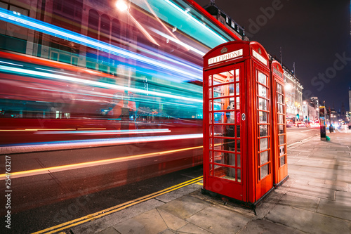 Poster de jardin Londres bus rouge Light trails of a double decker bus next to the iconic telephone booth in London