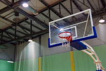 Poorly Washed Glass Basketball Backboard With A Basket In A Sports Complex. Green Background. Sport Theme. Copy Space. Lanterns On The Ceiling.