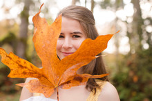 Portrait Of Smiling Woman Holding Maple Leaf While Standing In Forest During Autumn