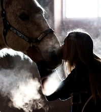 Low Key Image. Horse And Girl In Barn During Cold Winter Day, Steamy Breath Visible Back Lit From Window