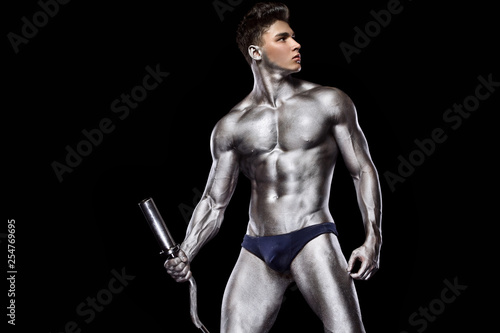 Fényképezés  Brutal strong muscular bodybuilder athletic man pumping up muscles with barbell on black background