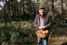Portrait Of Senior Man Holding Basket Of Mushrooms In Forest