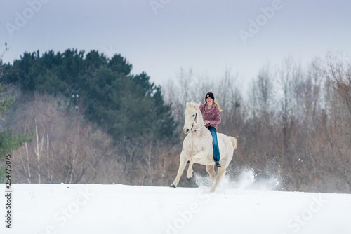 blonde young woman riding her horse through snow bareback on a winter day Wallpaper Mural