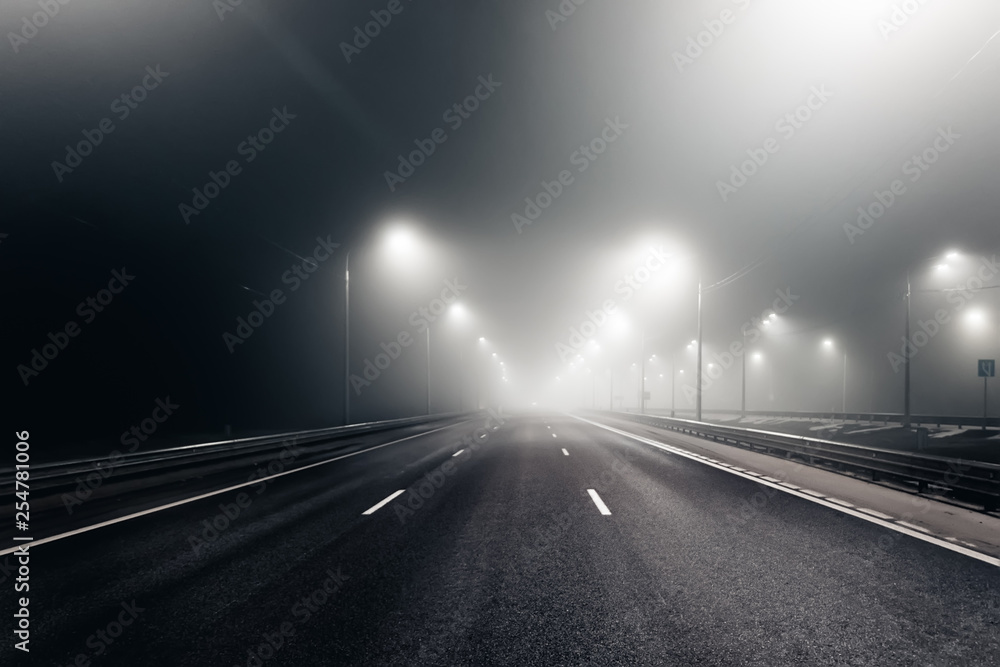 Fototapeta Foggy misty night road illuminated by street lights