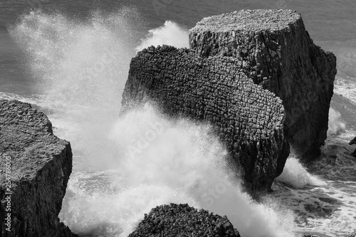 Fotografie, Obraz  Large sharp rocks with lots of detail and texture  as waves splash forcefully ag
