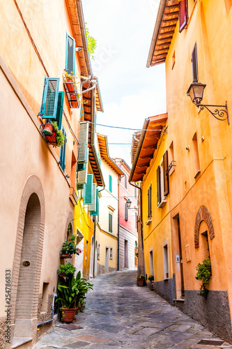 Chiusi, Italy street alley in small historic medieval town village in Umbria vertical view during sunny day with orange yellow bright vibrant colorful walls