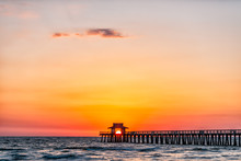 Naples, Florida Red Pink And Orange Sunset Skyscape In Gulf Of Mexico With Sun Setting Inside Behind Pier Framing With Horizon And Ocean Waves