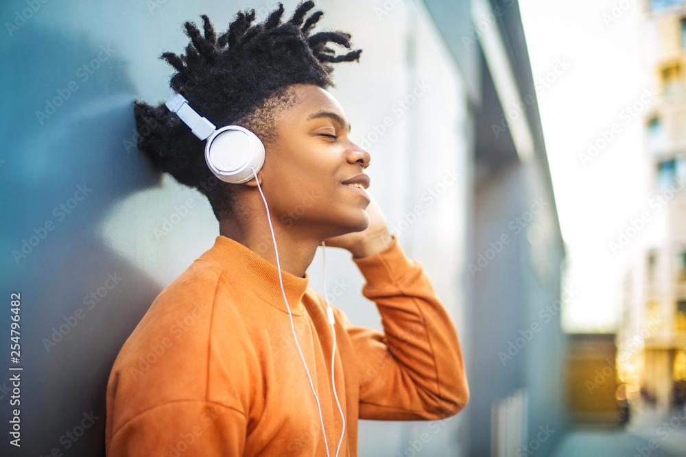 Fototapeta Cheerful guy listening music with the headphones