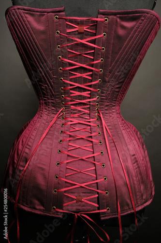 Fotografia Closeup of red vintage female corset on grey studio background