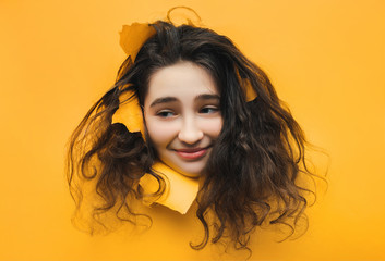 A funny teenage caucasian girl with problematic dry curly hair expresses displeasure on her face. Grin, smile, skeptical. Orange, yellow paper background.