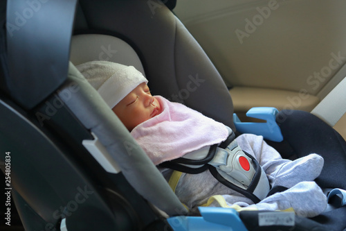 Fotografija cute newborn baby sleeping in car seat safety belt lock protection drive road tr