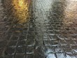 Wet dark brown stone tile on the floor. Lighting reflection on rough walkway surface.