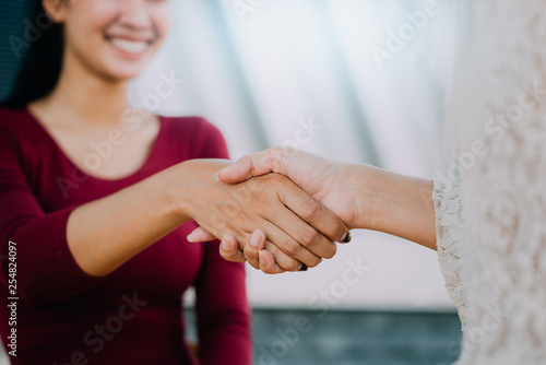 Fototapeta Negotiating business,Image of businesswomen Handshaking,happy with work,the woman she is enjoying with her workmate,Handshake Gesturing People Connection Deal Concept obraz