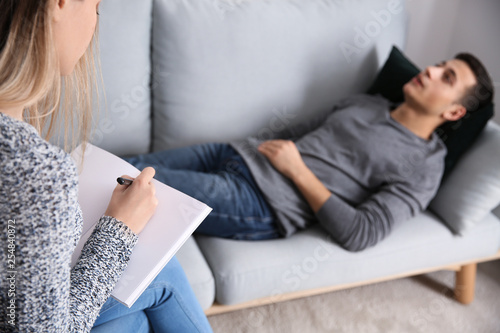 Fotografia, Obraz Female psychologist working with patient lying on sofa in her office