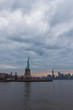 View of New York City skyline and Statue of Liberty with dramatic sky at dusk, New York, USA