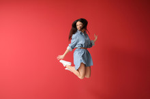 Beautiful Jumping Woman Against Color Background
