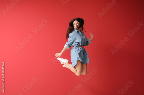 Fototapeta  Beautiful jumping woman against color background