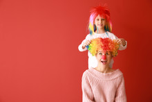 Woman And Little Girl In Funny Disguise On Color Background. April Fools' Day Celebration