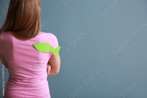 Photo Woman with paper fish on her back against color background