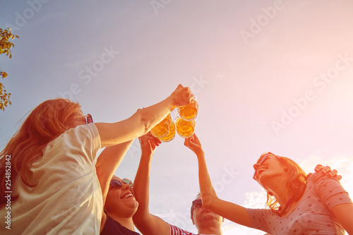 фотография Group of young people enjoying and cheering beer outdoors.